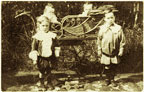 Photograph of young children with a pram.
