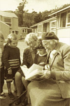 Photograph of old generation reading to young generation.